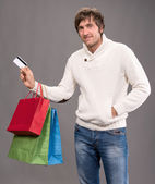 Man holding shopping bags and credit card — Stock Photo