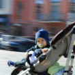 Llittle boy in a baby carriage — Stock Photo