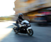 Motorcyclist in motion going down the street — Stock Photo