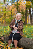 Old woman sitting on a log — Stock Photo
