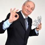 Elderly man holding dollars — Stock Photo #35357411