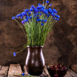 Still life with  blue cornflowers in vase and cherries — Stock Photo