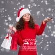 Smiling woman in santa hat with shopping bags — Stock Photo