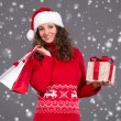 Smiling woman in santa hat with shopping bags and gift box — Stock Photo