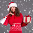 Smiling woman in santa hat with shopping bags and gift box — Stock Photo #35591521
