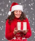 Lachende vrouw in kerstmuts met een doos van de gift — Stockfoto