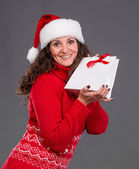 Smiling woman in santa hat with shopping bag — Stok fotoğraf