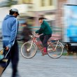 Man pushing a cart and man on bicycle — Stock Photo