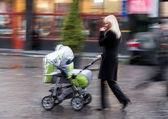 Mãe caminha com a criança no carrinho — Fotografia Stock