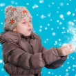 Llittle girl in winter clothes blowing snow — Stock Photo