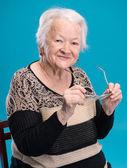 Old woman holding glasses — Foto de Stock