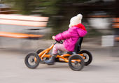 Girl racing in a pedal cart — Stock Photo