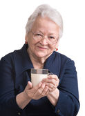 Healthy old woman holding a glass of milk — Stock Photo