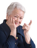 Smiling old woman pointing upwards — Stock Photo