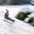 Small boy sledding at winter time — Stock Photo