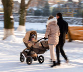 Parents walking with the child in the stroller — Stock Photo