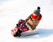 Small girl sledding at winter time — Stock Photo