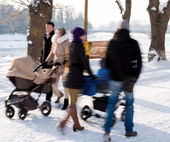Parents walking with children in the strollers — Stock Photo