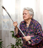 Old angry woman threatening with a cane — Stock Photo