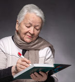 Senior woman writing notes in a notebook — Stock fotografie