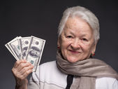 Old woman holding money in hands — Stock Photo