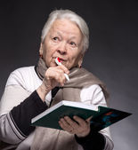 Senior woman writing notes in a notebook — Stockfoto