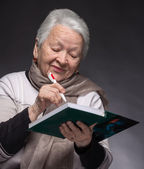 Senior woman writing notes in a notebook — Foto de Stock