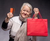 Happy old woman with shopping bags and credit card — Stock Photo
