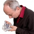 Old man looking at dollar bills — Stock Photo