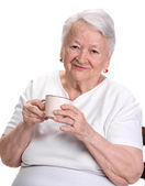 Old woman enjoying coffee or tea cup — Stock Photo