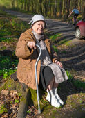 Old woman sitting on a stump — Stock Photo