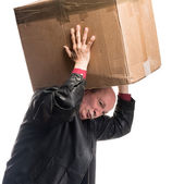 Senior man carries a heavy box — Stock Photo