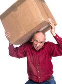 Senior man carries a heavy box — Stock Photo
