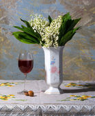 Lily of the valley in vase, glass of wine and candies — Stock Photo