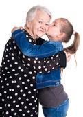 Granddaughter kissing her grandmother — Stock Photo