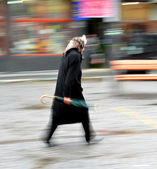 Woman walking in the street on a rainy day — Stock Photo