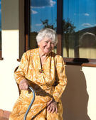 Smiling old woman sitting near the house — Stock Photo