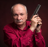 Senior man with a gun — Photo