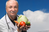 Male doctor holding vegetables — Stock Photo