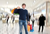 Smiling man n with shopping bags — Stock Photo