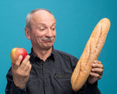 Doubting man with apple and baguette — Stock Photo