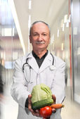 Senior male doctor holding vegetables — Stockfoto