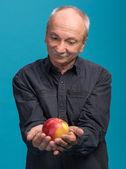 Senior hombre sosteniendo una manzana — Foto de Stock