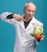 Male doctor holding vegetables — Stockfoto