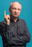 Portrait of senior man  pointing his forefinger up — Stock Photo