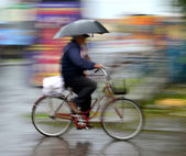 Cyclist in motion riding down the street on rainy day — Stock Photo
