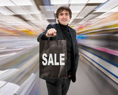 Smiling man with shopping bag — Stock Photo