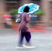Woman walking down the street on a rainy day  — Stock Photo