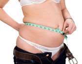 Overweight woman measuring waistline — 图库照片