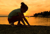 Silhouette of a little girl at the beach — Stock Photo